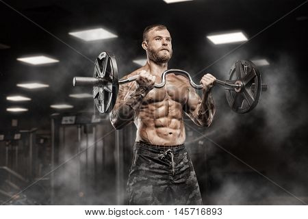 Strong Athletic Man bodybuilderl Torso showing muscles in gym