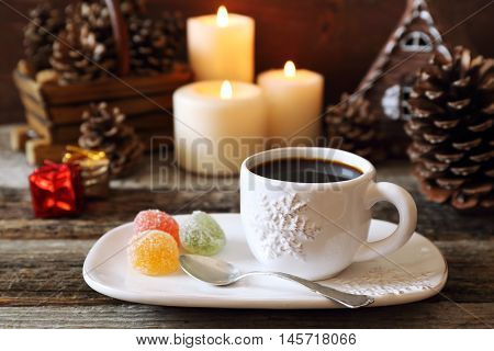 New Year composition: cup of coffee and pine cones burning candles and colorful candy