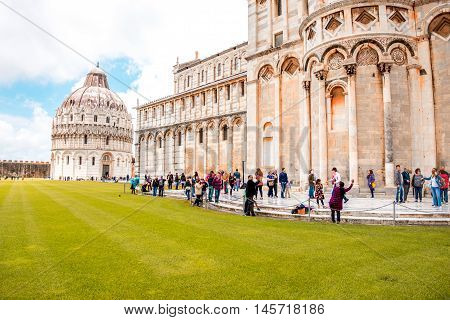 Pisa, Italy - June 02, 2016: Tourists near Pisa cathedral and baptistery on the field of Miracles in Pisa town in Italy