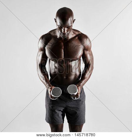 Muscular Male Fitness Model Holding Dumbbells