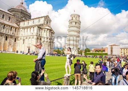 Pisa, Italy - June 02, 2016: Tourists near Pisa tower and cathedral on the field of Miracles in Pisa town in Italy