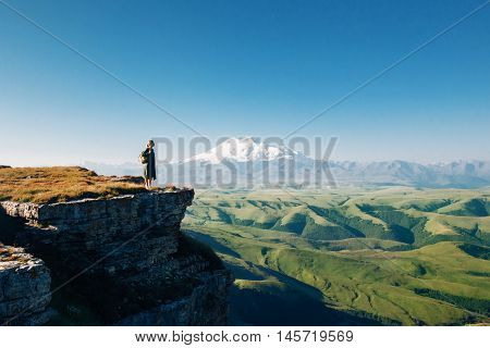 Traveler standing on top of Bermamyt plateau and looking on Elbrus mountain. Karachay-Cherkessia, Caucasus, Russia.