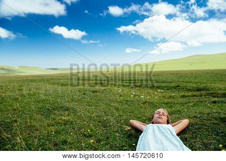 Tween girl relaxing on green grass in spring field, blue skies, idyllic scene