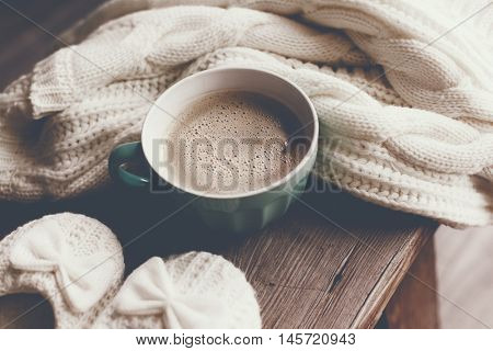 Cup of hot coffee on rustic wooden bench, closeup photo of warm sweater with mug and slippers, winter morning concept