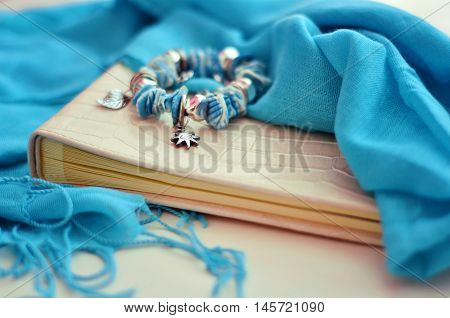 Photo album lies on a white background. Blue scarf covers album. Bracelet in marine style lies on the album.