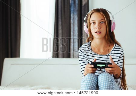 10 years old pre teen girl holding gaming console and playing on a sofa at home in the morning