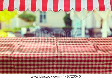 Empty table with red checked tablecloth and awing