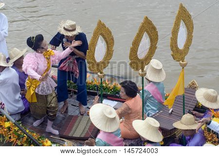 AYUTTHAYA, THAILAND - JULY 15, 2011: Unidentified people dancing show on the flower boats in candle floating parade, the unique annual candle festival of Buddhist lent  in Lad Chado, Ayutthaya, Thailand.