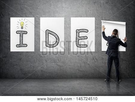Businessman putting up posters with letters on a concrete wall that form a 'idea' word. Business staff. Office clothes. Succesful management.