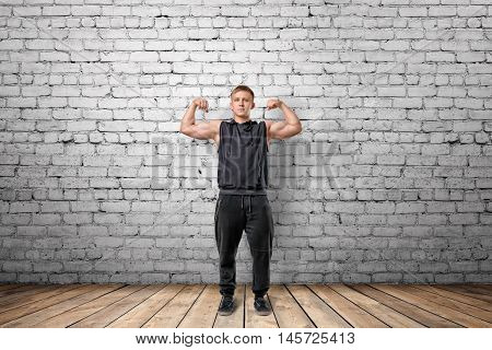 Front view of muscled young man showing his bicep muscles on the background of white brick wall. Wellbeing. Muscleman. Workout and fitness.