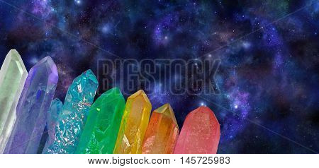 Deep Space Cosmic Aura Wands - wide dark blue outer space background with seven chakra colored crystal wands spanning bottom left corner diagonally providing plenty of copy space above