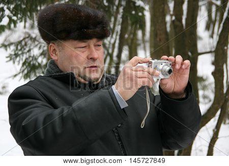 CUMAN UKRAINE - 19 January 2010: Ukrainian man in a fur cap and sheepskin coat photographed in the winter park