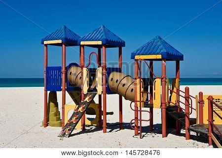 Kids Playground Equipment on a Sandy Beach with Ocean Background