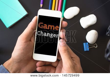 Game changer, text message on screen at hands take smartphone, black table with office supplies backdrop background . business concept.