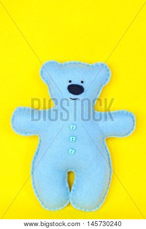 Handmade felt bear. Blue felt bear on yellow background, hand stitched toy, a craft out of felt