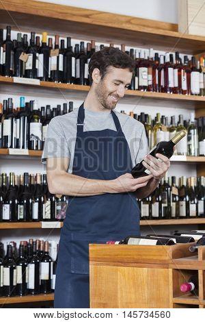 Salesman Reading Label Of Wine Bottle In Store