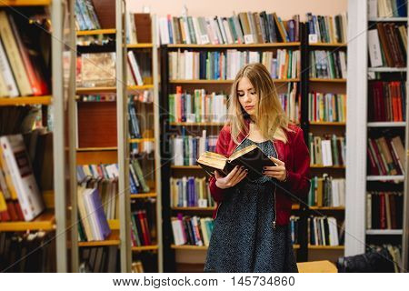 Female student reading a book between bookshelves in university library.