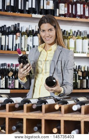 Mid Adult Woman Choosing Between Wine Bottles