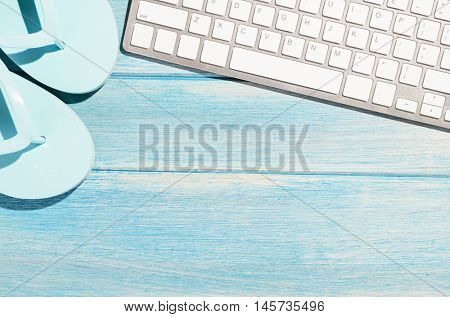white modern keyboard with beach accessories on blue wooden table
