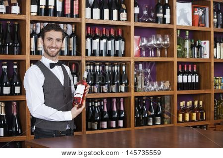 Male Bartender Holding Red Wine Bottle In Shop
