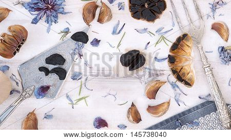 pretty black garlic background crop in 16x9 for headers and covers showing half cloves with silver fork and small blue flowers copy space bottom center