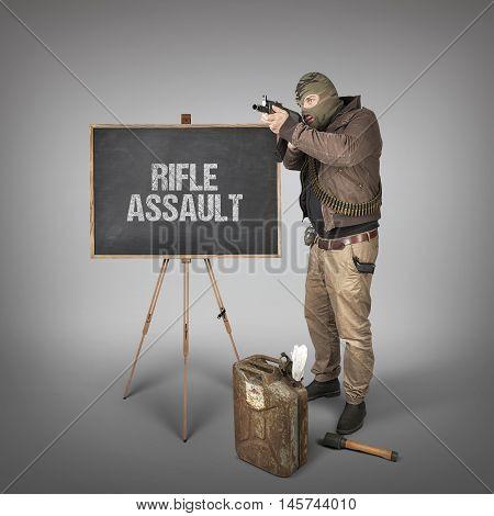 Rifle assault text on blackboard with terrorist holding machine gun