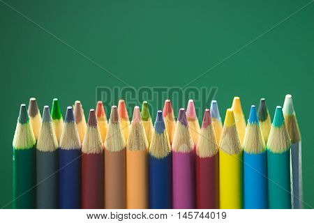 Line of colored pencils in front of a green chalk board.