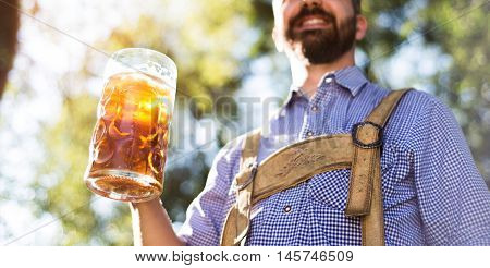 Unrecognizable young hipster man in traditional bavarian clothes holding a mug of beer. Oktoberfest. Sunny summer garden.