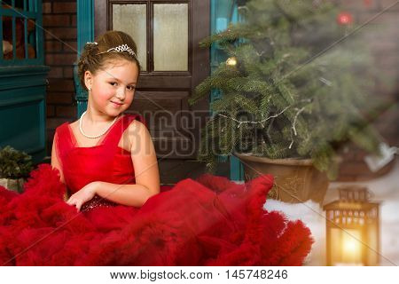 Little winter Princess in a precious crown in red dress welcomes New year and Christmas in enchanting holiday interior with decorated Christmas tree and artificial snow
