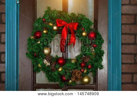 Christmas wreath on the door. Welcomes New year and Christmas in enchanting holiday interior with decorated fir-tree branches