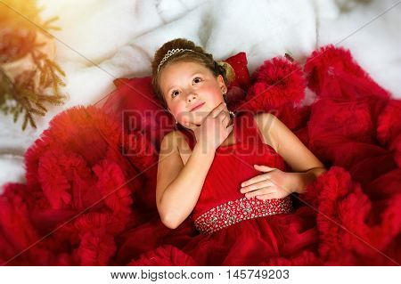 Little winter Princess in a precious crown in red dress lies on artificial snow. Welcomes New year and Christmas in enchanting holiday interior with Christmas tree