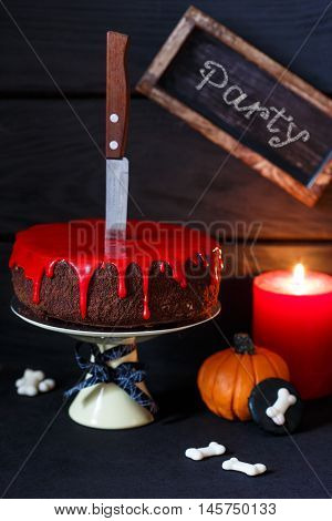Bleeding monster cake with knife on cakestand, pumpkin and candle.