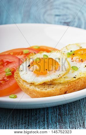Fried quail eggs with a toast and tomatoes strewed with fresh green onions in a white plate on a wooden turquoise surface.