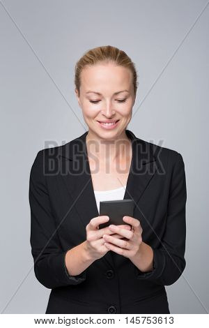 Beautiful young caucasian businesswoman in business attire using smart phone application. Studio portrait shot on grey background.