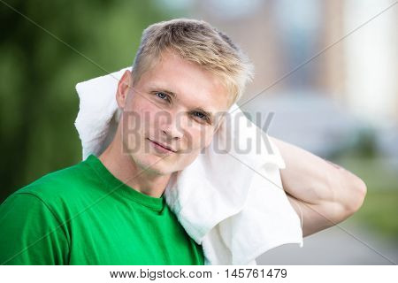 Tired man with white towel after fitness time and exercising in city street park at beautiful summer day. Sporty model caucasian ethnicity training outdoor.