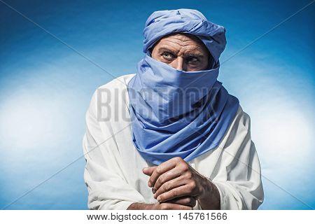Berber Man Wearing Blue Turban With White Robe. Leaning On Cane. Studio Shot.