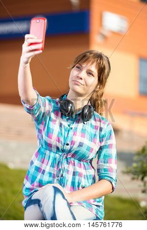 Happy young girl taking pictures of herself through cell phone, over collage campus. Selfie woman.