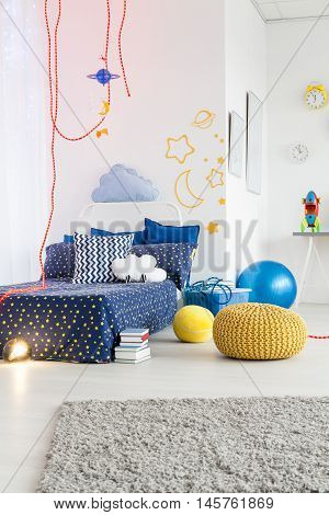 Cosy room for a young astronaut boy with cosmic themes on the walls and bedding