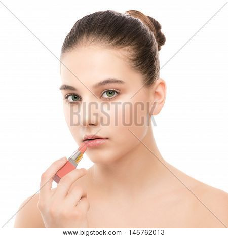 Portrait of beautiful young brunette woman with clean face. Beauty spa model girl with perfect fresh clean skin applying lipstick. Youth and skin care concept. Isolated on a white background.