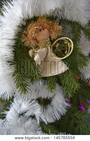 Christmas toy in the form of an angel. The toy is located on a fir-tree. An angel in gold clothes. The angel holds a psaltery.