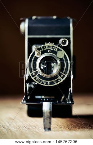 closeup of an old folding camera on a rustic wooden surface