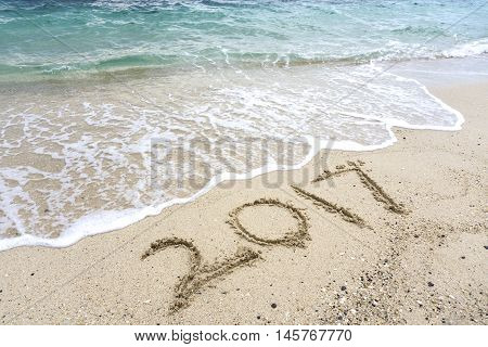 Number 2017 Written On A Sand Beach With Sea Waves, Happy New Year Concept.
