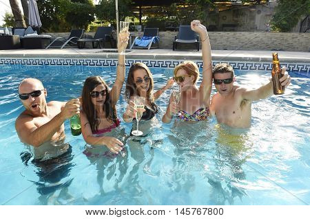 group of friends young happy attractive men and women in bikini having bath at hotel resort swimming pool drinking beer bottle having fun smiling playful in boys and girls summer party and holidays