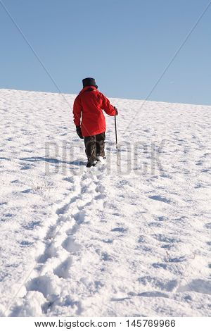 Woman hiking alone up a snow covered hill in winter