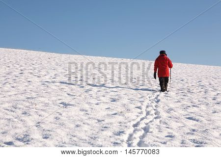 Woman walking alone up a snow covered hill in winter
