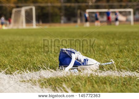 Standing sports shoe on a background of a football field with the players. Selective focus. Sport concept, despair, defeated