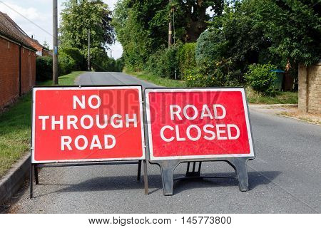 Road signs showing a street closed in the UK