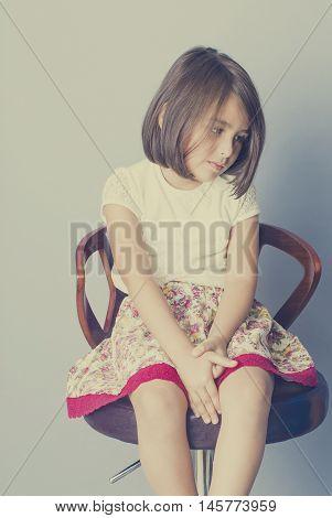thining girl sitting on stoool isolated in studio