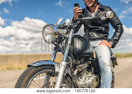 Making good time. Smiling biker enjoying weekends in country side on sunny day, using smartphone