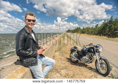 All I need is my bike. Handsome guy standing beside road near lake and holding smartphone, looking at camera and smiling with motorcycle in background